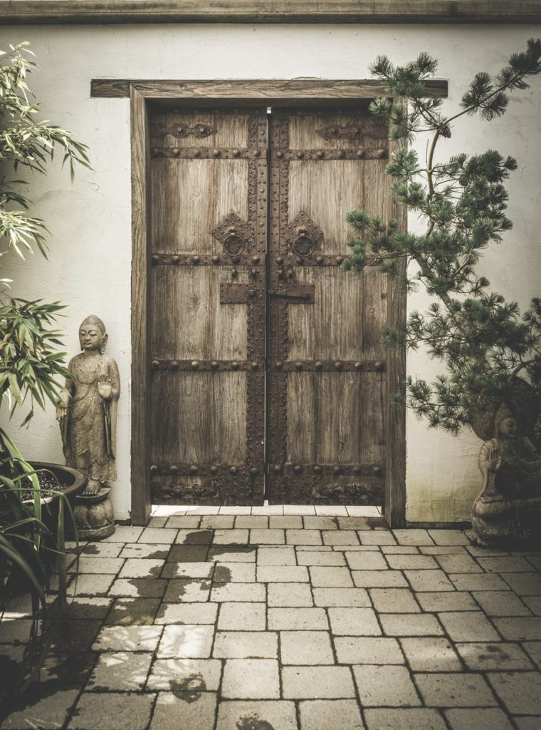 Porte en bois ornée de deux bouddhas.